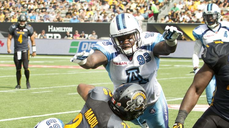 Tiger-Cats' Madu is tackled by Argonauts' Jones as teammate Johnson arrives to assist in their CFL Labour Day Classic football game in Hamilton