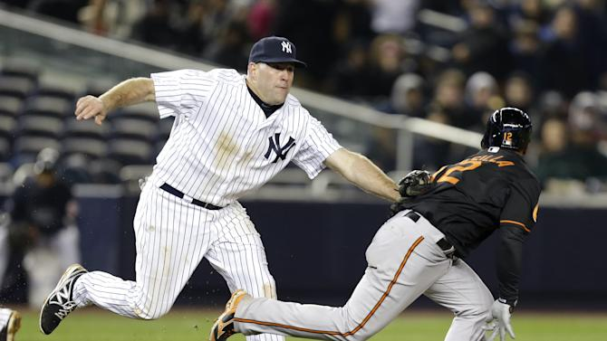 New York Yankees third baseman Kevin Youkilis, left, tags out Baltimore Orioles' Alexi Casilla for the second out of a triple play during the eight inning of a baseball game at Yankee Stadium in New York, Friday, April 12, 2013. (AP Photo/Julio Cortez)