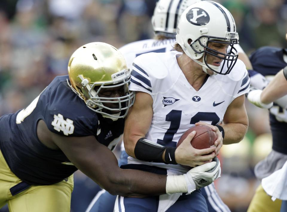 Notre Dame defensive end Kapron Lewis-Moore, left, sacks BYU quarterback Riley Nelson during the first half of an NCAA college football game in South Bend, Ind., Saturday, Oct. 20, 2012. (AP Photo/Michael Conroy)