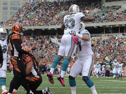 Miami Dolphins running back Daniel Thomas (33) jumps in the arms of tackle Jake Long after Thomas scored a touchdown in the first half of an NFL football game against the Cincinnati Bengals, Sunday, Oct. 7, 2012, in Cincinnati. (AP Photo/Michael Keating)
