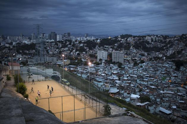 "In this March 7, 2014 photo, boys play soccer in the Sao Carlos slum after sunset in Rio de Janeiro, Brazil. The first thing Brazilian kids often do before pick-up games is play ""rock, scissors,"