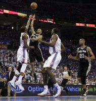 San Antonio Spurs guard Tony Parker (9), of France, shoots over Oklahoma City Thunder forward Kevin Durant (35) as Thunder&#39;s Serge Ibaka (9) and Spurs&#39; Tim Duncan (21) move in during the first half of Game 4 in the NBA basketball playoffs Western Conference finals, Saturday, June 2, 2012, in Oklahoma City. (AP Photo/Eric Gay)