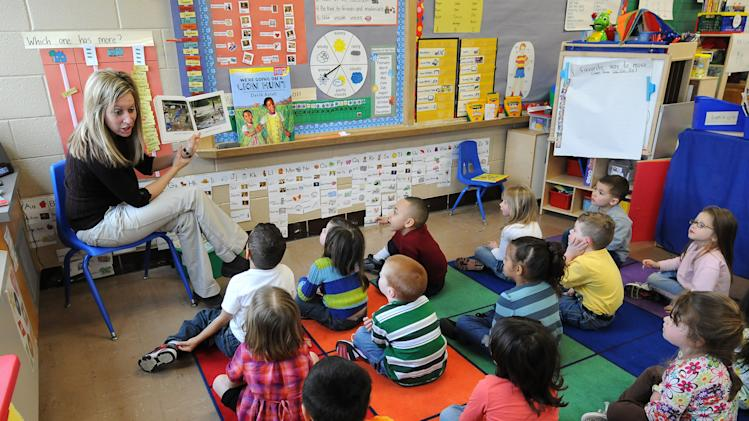 FILE - In this March 29, 2011, file photo four and five-year-old preschool students listen to their teacher, Angie Clark, read at a Des Moines Iowa elementary school. Within the last year national polls in the United States indicate Americans still think a lot alike and share core values: Nine out of 10 call themselves very patriotic, believe in God, value higher education, and admire those who get rich through hard work. Seven out of 10 want to raise the minimum wage, and similar numbers support building the Keystone XL pipeline, and making preschool available to every child.  (AP Photo/Steve Pope, File)