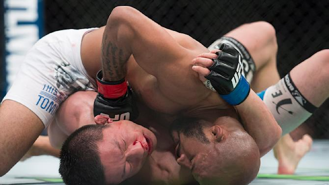 Demetrious Johnson, right, from the United States, lands a blow to the head of Kyoji Horiguchi, from Japan, during their UFC 186 mixed martial arts flyweight title fight in Montreal, Saturday, April 25, 2015. (Graham Hughes/The Canadian Press via AP)