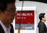 Passers-by walk past a branch of Nomura Securities in Tokyo