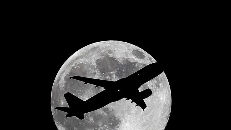 "One day before a ""supermoon,"" Virgin America flight VX415 from New York (JFK) to Los Angeles (LAX) crosses the waxing gibbous moon on its final approach to Los Angeles Airport as viewed from Whittier, Calif., Friday, July 11, 2014. (AP Photo/Nick Ut)"
