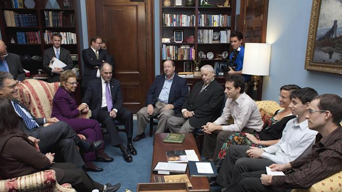 Former US hikers imprisoned in Iran, seated at right, Shane Bauer, Josh Fattal and Sarah Shourd and Fattal's brother Alex, meet with Sen. Al Franken, D-Minn., and Sen. Robert Casey, D-Pa., on Capitol Hill in Washington, Wednesday, Oct. 12, 2011. (AP Photo/Harry Hamburg)