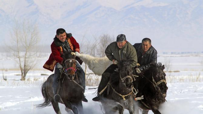 Kyrgyz men ride horses as they fight for a slaughtered goat during a Buzkashi event in Altay
