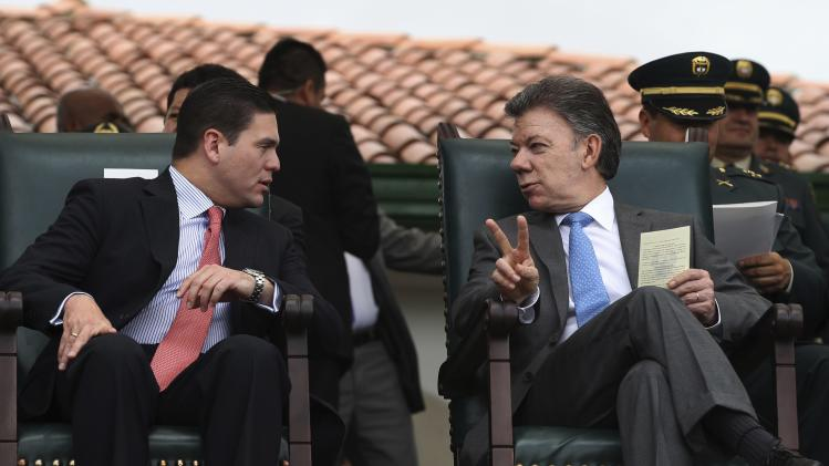 Colombia's President Santos listens to Defence Minister Juan Carlos Pinzon during a promotion ceremony at a military school in Bogota