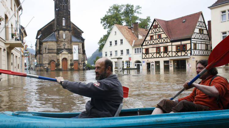 Two men in a boat  cross the  flooded market place of the city of  Wehlen at the river Elbe , Germany, Tuesday,  June 4, 2013. After heavy rainfalls, swollen rivers flooded areas in Germany, Austria , Switzerland and Czech Republic. (AP Photo/Markus Schreiber)