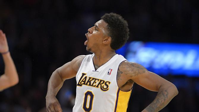 Los Angeles Lakers forward Nick Young celebrates after hitting a three point shot during the second half of an NBA basketball game against the Orlando Magic, Sunday, March 23, 2014, in Los Angeles. The Lakers won 103-94