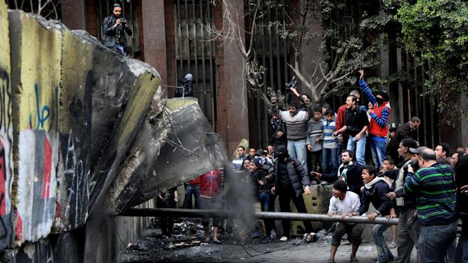 Egyptian protesters try to tear down a cement wall built to prevent them from reaching parliament and the Cabinet building near Tahrir Square, in Cairo, Egypt, Thursday, Jan. 24, 2012. Egypt's black-clad riot police fired tear gas in fierce dawn clashes with dozens of protesters. The violence which was soothed hours later in central Cairo comes on eve of the second anniversary of Egypt's Jan. 25 uprising, which toppled longtime authoritarian president Hosni Mubarak in 2011. (AP Photo/Hussein Tallal)