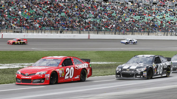 Matt Kenseth (20) and Jimmie Johnson (48) drive down pit row during a NASCAR Sprint Cup series auto race at Kansas Speedway in Kansas City, Kan., Sunday, April 21, 2013. (AP Photo/Orlin Wagner)
