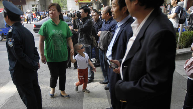 A child wearing sunglasses tries to get past onlookers and journalists gathered outside a hospital where blind Chinese activist Chen Guangcheng is believed to be seeking treatment in Beijing, China, Wednesday, May 2, 2012.  Chen who sparked a diplomatic tussle by holing up in the U.S. Embassy in Beijing for six days emerged Wednesday after U.S. officials said China had assured his safety. (AP Photo/Ng Han Guan)
