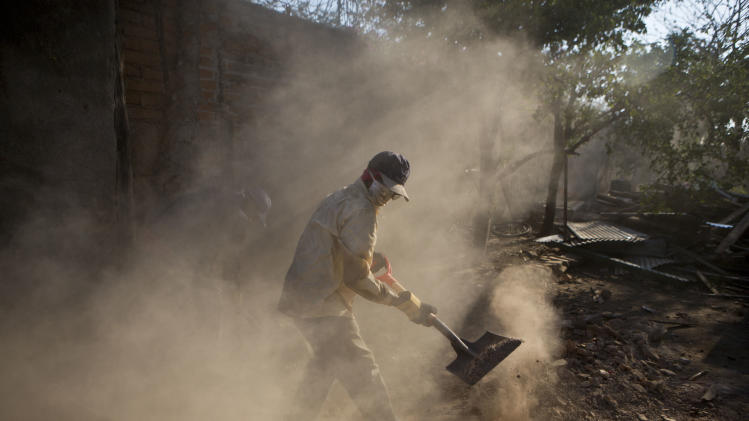 A city worker helps clear away debris caused by recent earthquakes in Nagarote, Nicaragua, Wednesday, April 16, 2014. The government continues to recommend residents sleep outside their homes after a series of earthquakes and aftershocks have shaken the area since last week. (AP Photo/Esteban Felix)