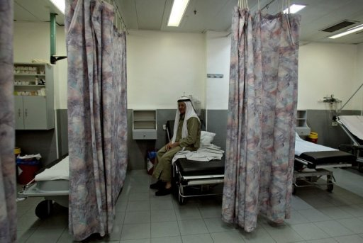 A Palestinian sits on a bed at the Makassed Hospital in Jerusalem. The hospital, which is threatened with closure due to a financial crisis, is facing an open-ended strike by its staff members who haven't been receiving wages for the past two months