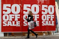 A shopper walks past a sale sign on New Oxford Street in London, in March. Britain&#39;s recession is worse than previously thought, as revised official figures show that the economy shrank by more than expected in the first quarter of this year