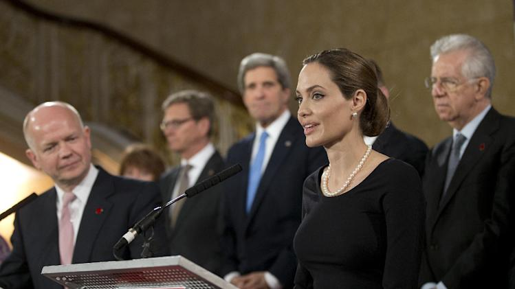 Flanked by G8 Foreign Ministers, US actress Angelina Jolie, in her role as UN envoy, talks during a news conference regarding sexual violence against women in conflict, during the G8 Foreign Ministers meeting in London, Thursday, April, 11, 2013. The ministers are meeting in London as Britain currently holds the G8 Presidency, with the heads of government G8 meeting set for June in Northern Ireland.(AP Photo/Alastair Grant, pool)