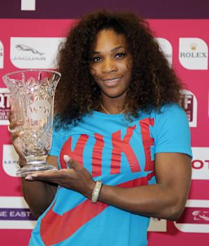 Serena Williams of the United States poses with a trophy given to her by the WTA Tour after the 31-year-old American reclaimed the world number one ranking following her WTA Qatar Open tennis quarter-final match against Czech Republic's Petra Kvitova in the Qatari capital, Doha on Friday, Feb. 15, 2013. (AP Photo/Osama Faisal)