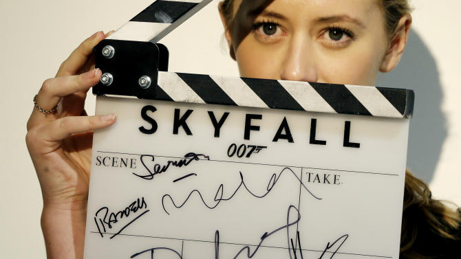 A film clapperboard used during the filming of the upcoming James Bond movie 'Skyfall'  and signed by director Sam Mendes, Daniel Craig, who plays James Bond, Naomie Harris, Javier Bardem and Berenice Marlohe is held by a Christie's auction house employee during a press preview of items in a James Bond movie memorabilia charity auction at Christie's auction house in London, Friday, Sept. 28, 2012. The clapperboard is estimated at 800-1,000 pounds (US$ 1,200-1800 euro 900-1300) and will be sold in aid of UNICEF. (AP Photo/Alastair Grant)