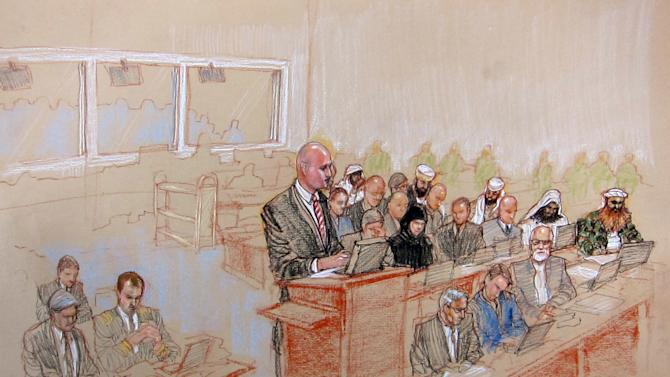 In this pool photo of a sketch by courtroom artist Janet Hamlin and reviewed by the U.S. Department of Defense, attorney James Connell, center, Pentagon-appointed defense lawyer for Sept. 11 co-conspirator Ammar al Baluchi, questions retired U.S. Navy Vice Admiral Bruce MacDonald, who last served as the 40th Judge Advocate General of the Navy, via video conference during the pretrial hearings at the Guantanamo Bay U.S. Naval Base in Cuba, Monday, June 17, 2013. Five Guantanamo Bay prisoners accused of helping orchestrate the Sept. 11 terrorist attacks returned to court Monday as arguments resumed over the preparations for a trial that remains distant. At far right is the self-proclaimed terrorist mastermind Khalid Sheikh Mohammed. (AP Photo/Janet Hamlin, Pool)
