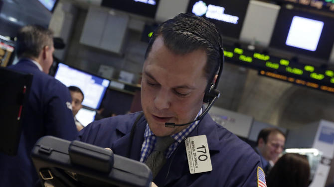 Trader Michael Zicchinolfi works on the floor of the New York Stock Exchange, Thursday, Dec. 19, 2013. Stocks edged lower in early trading Thursday, pulling back from record levels. (AP Photo/Richard Drew)