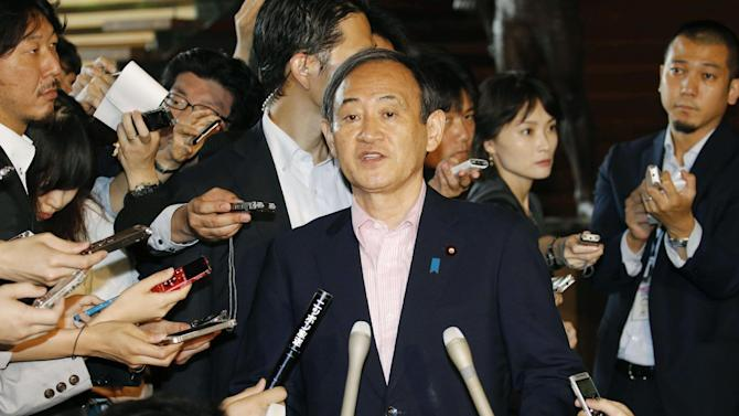 Japan's Chief Cabinet Secretary Yoshihide Suga, center, answers a reporter's question on an eruption of a volcano in southern Japan, at prime minister's official residence in Tokyo Friday, May 29, 2015. Mount Shindake on Kuchinoerabu island erupted in spectacular fashion on Friday, spewing towering black-gray clouds into the sky. Authorities ordered residents to evacuate the island. (Kyodo News via AP) JAPAN OUT, MANDATORY CREDIT