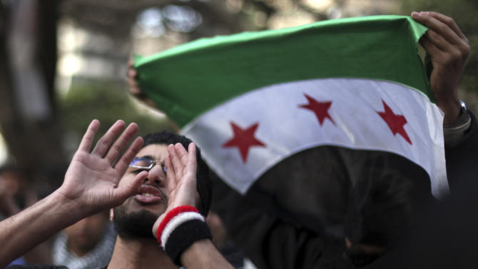 Egyptian and Syrian protesters, one holding the Syrian revolutionary flag, protest against Iran's President Mahmoud Ahmadinejad, during his visit to Egypt for the 12th summit of the Organization of Islamic Cooperation, in front of the Iranian diplomatic representation office in Cairo, Egypt, Wednesday, Feb. 6, 2013. (AP Photo/Khalil Hamra)