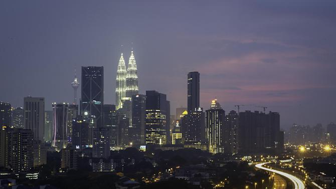 In this Friday, March 1, 2015 photo, Malaysia's landmark the Petronas Twin Towers and Kuala Lumpur Tower is seen illuminated during dusk in Kuala Lumpur, Malaysia on outside Kuala Lumpur, Malaysia. Two airplane catastrophes put Malaysia on the map in a bad way in 2014. But it didn't hurt the country's tourism, and the higher visibility may even have helped: visitor numbers had their strongest growth in years. (AP Photo/Joshua Paul)