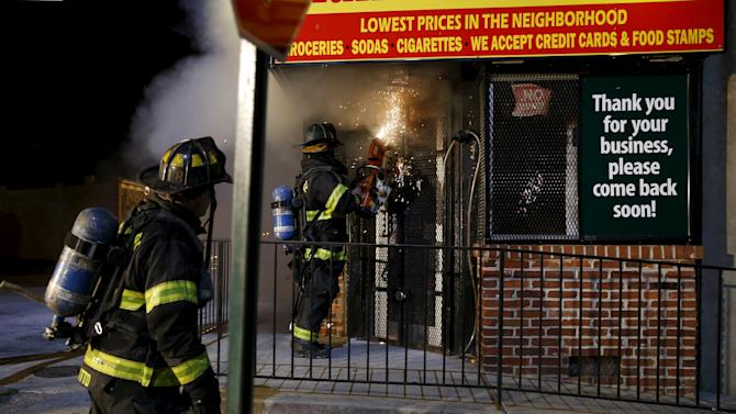 A Baltimore firefighter watches as a colleague cuts his way into a burning convenience store with a saw to attack a fire set by rioters at East Biddle Street and Montford Avenue in Baltimore