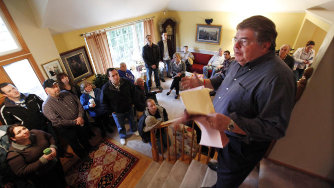 State Republican chairman Kirby Wilbur stands atop stairs in his home to explain to caucus attendees the process Saturday, March 3, 2012, in Duvall, Wash. Wilbur hosted five precincts at his home. Republicans crowded homes, churches and town halls across the state Saturday for Washington's GOP presidential caucuses, the first meaningful party contests in recent memory. While the caucuses are a nonbinding contest, state Republicans say it could create momentum for the four candidates on their last stop before Super Tuesday, when voting takes place in 10 states. (AP Photo/Elaine Thompson)