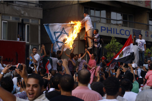 Egyptian activists burn a depiction of an Israeli flag as they demolish a concrete wall built around a building housing the Israeli embassy in Cairo, Egypt, to protect it against demonstrators, Friday, Sept. 9, 2011. Hundreds of Egyptian protesters tore down parts of a graffiti-covered security wall that had recently been put up near the entrance of the Israeli Embassy in Cairo. Egyptian security forces did not intervene as crowds climbed the embassy security wall, pummeled it with hammers and tore away large sections of the barrier. (AP Photo/Khalil Hamra)