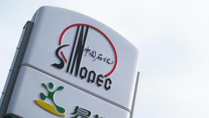 A Sinopec logo is seen on top of a logo of Easy Joy store at a gas station in Beijing