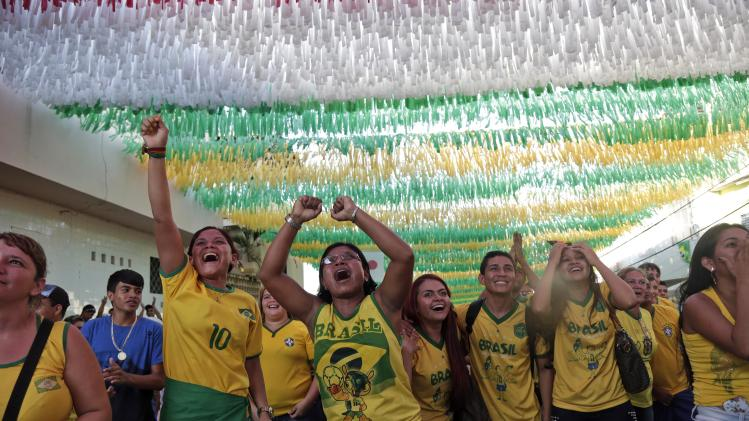 Fans celebrate a goal by Brazil as it plays Cameroon during the 2014 soccer World Cup in Manaus, Brazil, Monday, June 23, 2014. (AP Photo/Marcio Jose Sanchez)