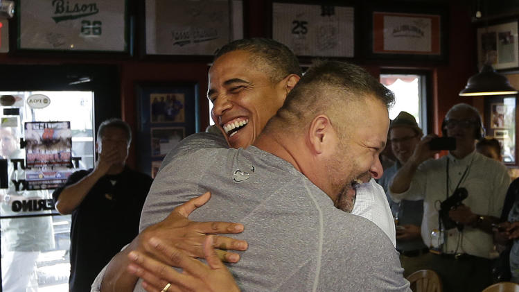 "In this photo taken Sept. 9, 2012, President Barack Obama, right, is hugged by Scott Van Duzer, owner of Big Apple Pizza and Pasta Italian Restaurant in Ft. Pierce, Fla. Obama's handlers let the muscular restaurant owner hoist the president off the ground in a big bear hug during a drop-by visit. ""Look at these guns!"" Obama enthused about the man's biceps. Every day, the ground troops of Team Obama and Team Romney set out in pursuit of a common goal: winning the day. Everyone poses for the camera.  (AP Photo/Pablo Martinez Monsivais)"