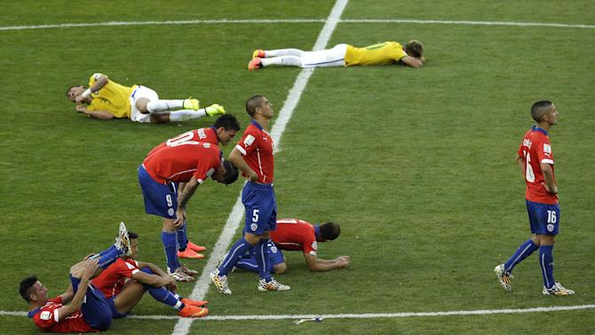 Players of Chile, front, and Brazil react after Chile's Gonzalo Jara missed to score from the penalty spot during the World Cup round of 16 soccer match between Brazil and Chile at the Mineirao Stadium in Belo Horizonte, Brazil, Saturday, June 28, 2014. Brazil won 3-2 on penalties after the match ended 1-1 draw after extra-time
