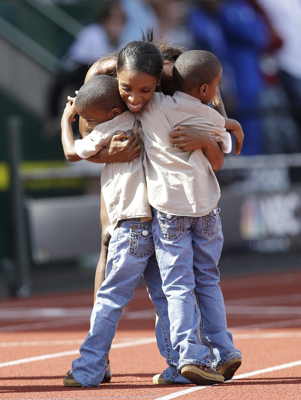 Lashinda Demus hugs her sons Dontay, right, and Duaine after finishing first in the women's 400 meter hurdles at the U.S. Olympic Track and Field Trials Sunday, July 1, 2012, in Eugene, Ore. (AP Photo/Marcio Jose Sanchez)