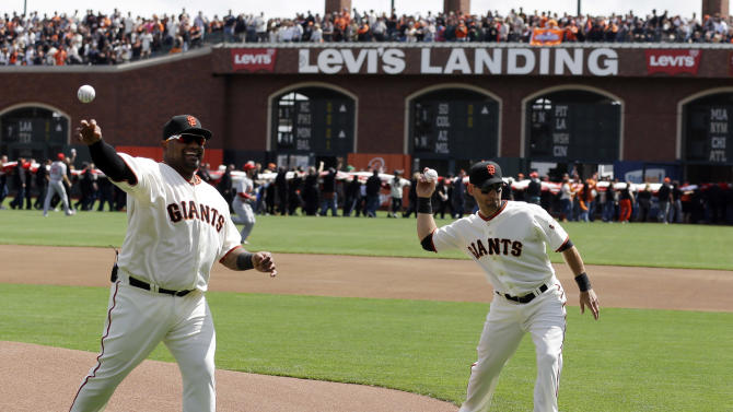 San Francisco Giants third baseman Pablo Sandoval, left, and second baseman Marco Scutaro throw the ceremonial first pitch before a baseball game against the St. Louis Cardinals on Friday, April 5, 2013 in San Francisco. (AP Photo/Marcio Jose Sanchez, Pool)