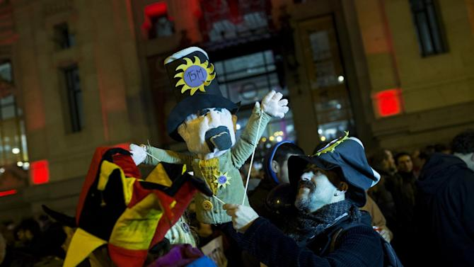 """A man, holding a puppet, gathers with others outside Madrid city hall in support of two puppeteers who were detained without a bail last Friday for using a sign saying, """"Long Live Alka ETA,"""" in a word-play reference to Spain's armed Basque group ETA and al-Qaida, in Madrid, Wednesday, Feb. 10, 2016. A Spanish court on Wednesday ordered the release of two puppeteers jailed since last week for allegedly praising terrorism in a controversial Carnival show funded with public money. (AP Photo/Francisco Seco)"""