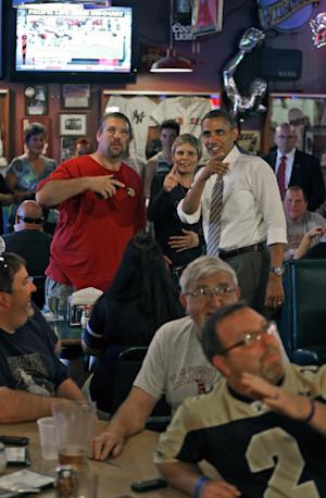 President Barack Obama, right, stop to greet patrons watching college football at Bob Roe's Point After Pizza during an unscheduled visit, Saturday, Sept. 1, 2012, in Sioux City, Iowa. (AP Photo/Pablo Martinez Monsivais)