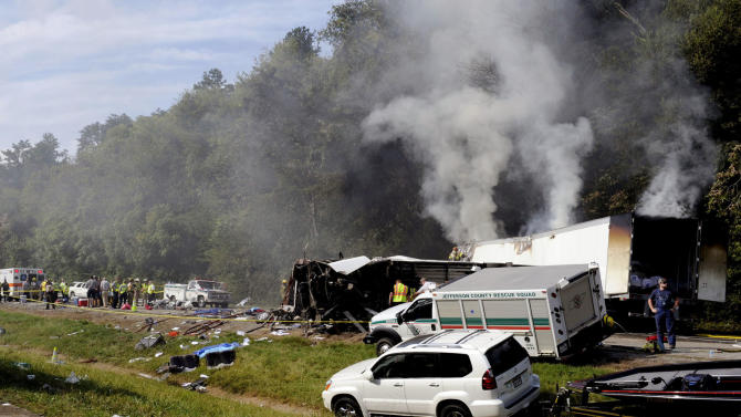 Emergency personnel search the scene near a collision involving a bus on I-40, in Dandridge, Tenn, on Wednesday, Oct. 2, 2013. A spokeswoman for Tennessee's Safety Department says there are multiple fatalities and injuries in an interstate bus crash between a passenger bus, a tractor-trailer and another vehicle. (AP Photo/The Knoxville News Sentinel, Michael Patrick)