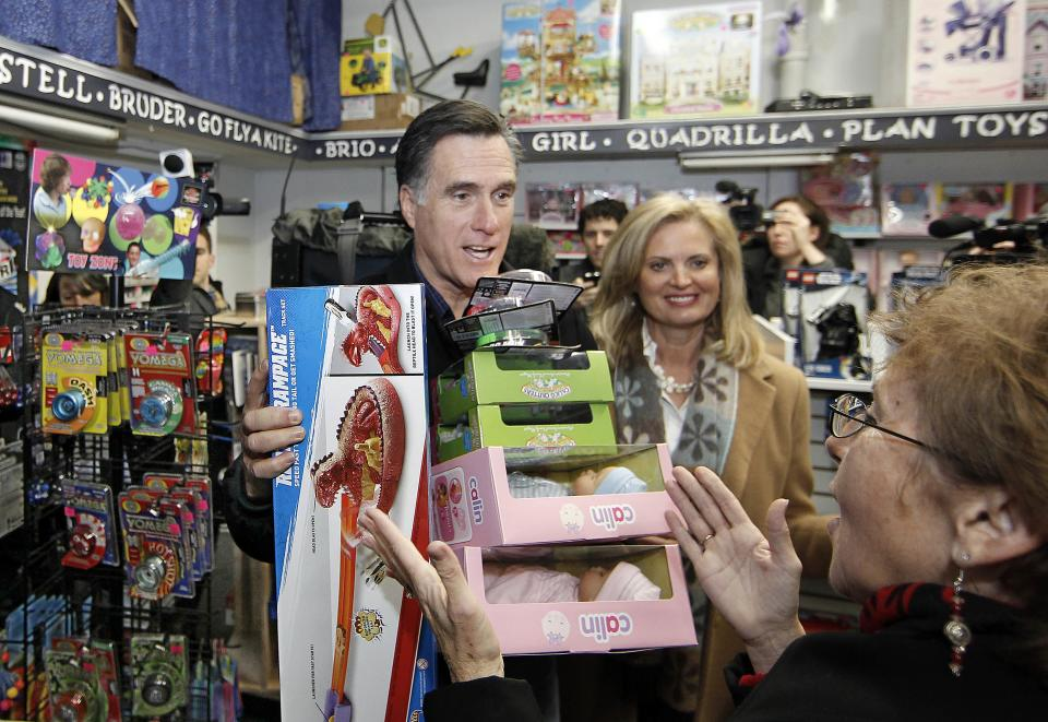 "Republican presidential candidate, former Mass. Gov. Mitt Romney and his wife Ann Talk with another customer while shopping for ""Toys For Tots"" in The Toy Store in Concord, N.H. Friday, Dec. 23, 2011. (AP Photo/Winslow Townson)"