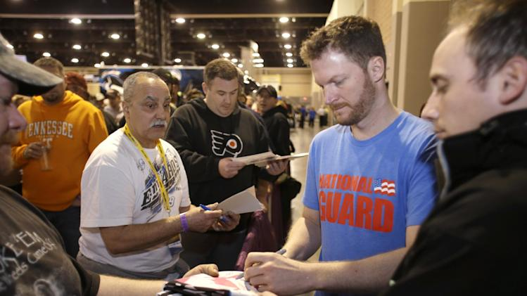 Dale Earnhardt Jr. signs autographs for fans as he makes his way out of the convention center following his autograph session during NASCAR Preview 2013, Saturday Feb. 9, 2013, in Charlotte, N.C. (AP Photo/Bob Leverone)