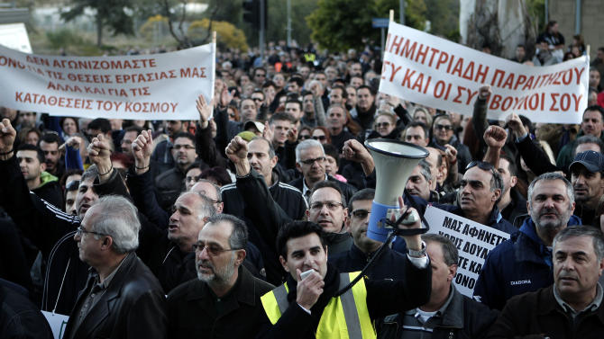 """Bank employees protest outside the ministry of finance on Saturday, March 23, 2013. Thousands of bank employees took part in a protest that ended outside the Cypriot parliament. Politicians in Cyprus were racing Saturday to complete an alternative plan raising funds necessary for the country to qualify for an international bailout, with a potential bankruptcy just three days away. Banner at left reads: We fight not only for our jobs but also for people's savings"""" and banner at right reads: """"Dimitriadis resign, you and your consultants"""". (AP Photo/Petros Giannakouris)"""