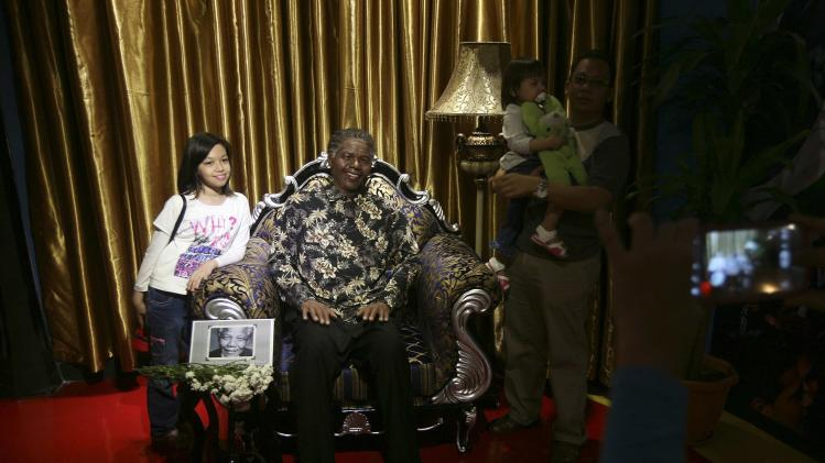 Visitors pose with a wax sculpture of late former South African President Nelson Mandela at the i-City Red Carpet Wax Museum in Shah Alam