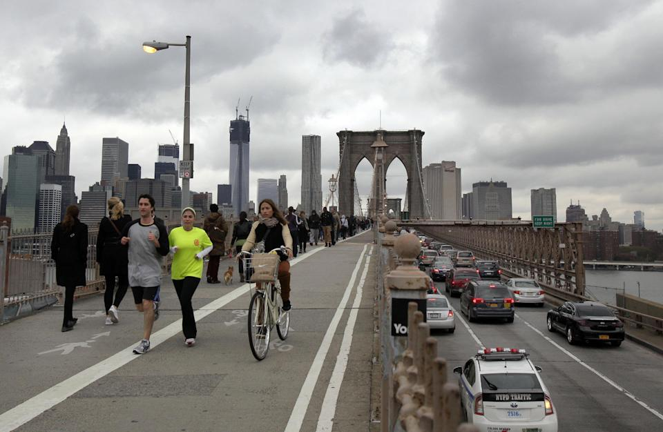 Commuters cross New York's Brooklyn Bridge, Wednesday, Oct. 31, 2012. Morning rush-hour traffic appeared heavier than on an ordinary day as people started to return to work in a New York without functioning subways. Cars were bumper to bumper on several major highways.  (AP Photo/Richard Drew)