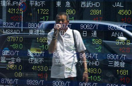 A man looks at stock prices displayed at a board showing market indices in Tokyo