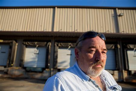 Former factory employee Richard Smith stands in front of factory owned by Platinum that was shut down by the company in 2010