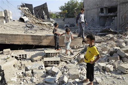 Boys walk on the rubble of a building hit by what activists said was shelling by forces loyal to Syria's President Bashar al-Assad, in the Duma neighbourhood of Damascus September 4, 2013. REUTERS/Bassam Khabieh