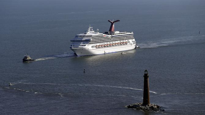 The disabled Carnival Lines cruise ship Triumph is towed to harbor off Mobile Bay, Ala., Thursday, Feb. 14, 2013. The ship with more than 4,200 passengers and crew members has been idled for nearly a week in the Gulf of Mexico following an engine room fire. (AP Photo/Gerald Herbert)